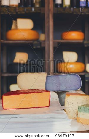 Cheese assortment closeup. Coloured pesto gouda and parmesan on counter at shop, cheese grocery background