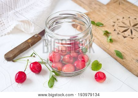 Fresh cherry fruits in a glass jar.