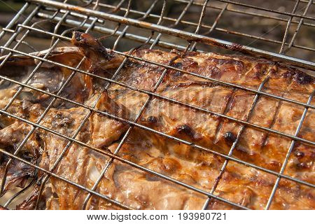 Close Up View Of Fresh Fish With Sauce Cooked On An Open Flame Grill..