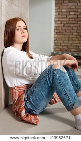 Casual ginger girl sitting on floor at home, looking at camera.