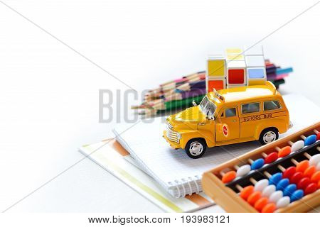 Close up view of yellow bus colorful back to school supplies border over white table. Mental arithmetic. Space for text.