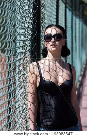 Woman sexy brunette with pretty face in black sunglasses and fashion swimsuit underwear with decollete posing near fence with net shadow on her
