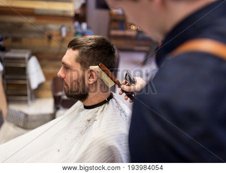 grooming, hairdressing and people concept - man and barber with trimmer and brush cleaning hair at barbershop