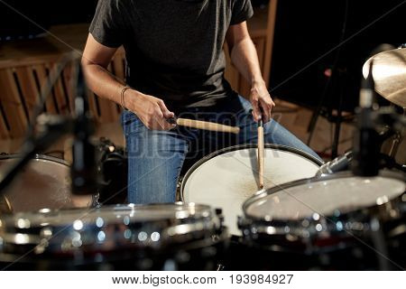 music, people, musical instruments and entertainment concept - male musician playing drums at concert or studio