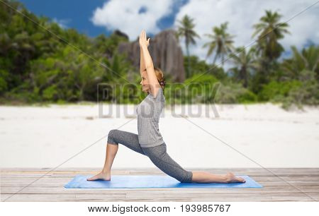 fitness, sport and people concept - happy woman doing yoga in low lunge pose on mat over exotic tropical beach background