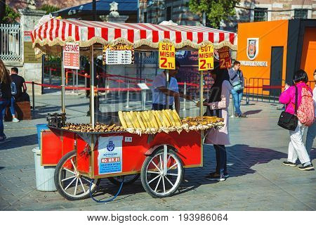 ISTANBUL TURKEY - MAY 2 2017: Seller of street fast food with boiled and grilled corn and chestnut on traditional turkish cart. Near Hagia Sophia
