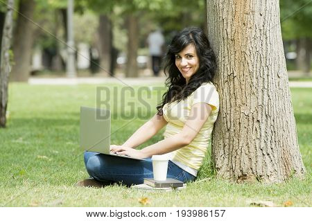Attractive beautiful latin woman happy working on her laptop or computer in a uni campus or green park