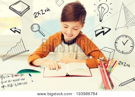 education, childhood, people, homework and school concept - happy student boy reading book or textbook at home over mathematical doodles poster
