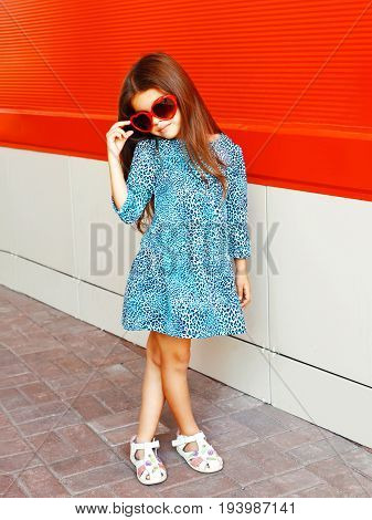 Fashion Beautiful Little Girl Child Wearing A Leopard Dress With Sunglasses On A Red Background