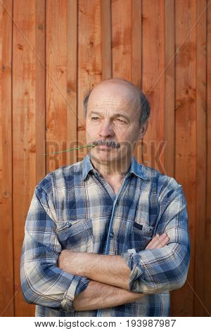 portrait of thoughtful middle aged man outdoors on wooden background
