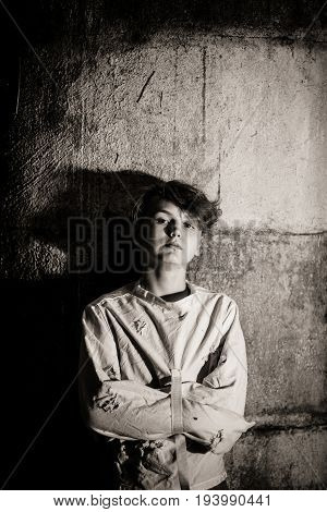 Atmospheric monochrome image of an intense staring young boy constrained in a straight jacket leaning against on old cement wall in a retro lunatic asylum or psychiatric clinic