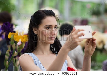 Portrait of young attractive woman doing selfie on phone outdoors
