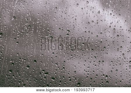 Rain drops on window glasses background. Natural Pattern of raindrops isolated on cloud background.