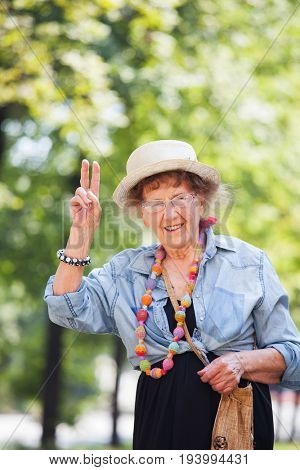 Happy granny outdoors. Old woman walking. Seniors