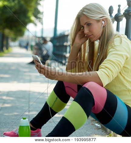Attractive female runner using mobilephone while resting.