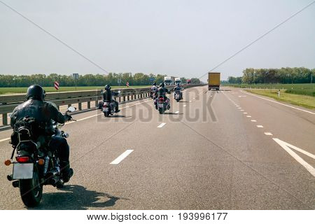 A group of bikers are driving along the highway.