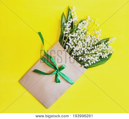 Lilies of the valley in a craft envelope tied with a green ribbon on a white surface top view