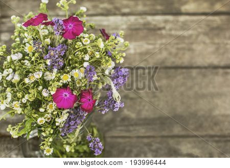 Bouquet of wildflowers on the background of a wooden surface