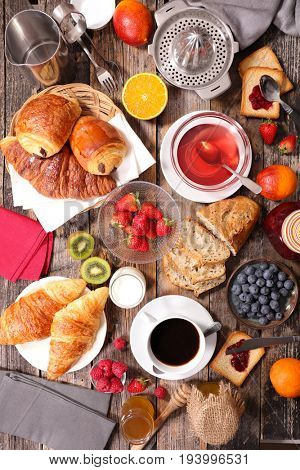 breakfast composition with coffee,tea,croissant and fruits