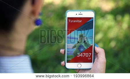 Samara, Russia - July 4, 2017: woman playing pokemon go on his iphone 6s plus. pokemon go multiplayer game with elements of augmented reality.