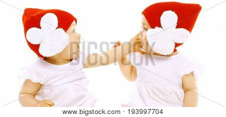 Closeup Portrait Two Baby Twins In Red Hats Face To Face Fighting On A White Background