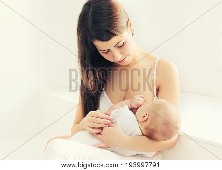 Happy Mother Feeding Breast Her Baby At Home In White Room
