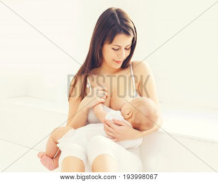 Happy Young Mother Feeding Breast Her Baby At Home In White Room