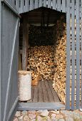 Wooden shed filled with chopped firewood piles poster