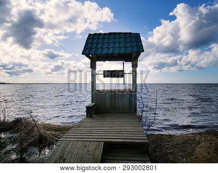 Old Draw Well On Shore Of Lake. View Of Water Through Well Gate. Paradox Of Water In The Water. Conc