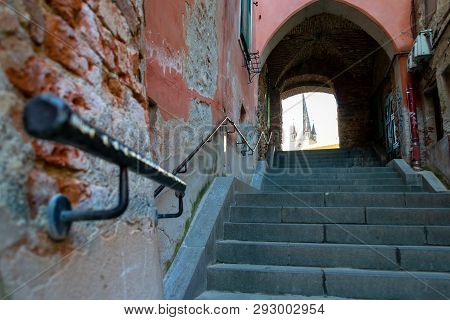 Old narrow street with shriveled brick walls, cement stairs and a black metal handrail pointing up towards an archway with a a few church towers in the back - Sibiu, Transylvania, Romania poster
