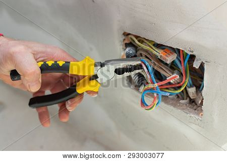 Electricians Hand Holding Electric Wires, Electric Socket On The Wall - Renovation, In Construction,