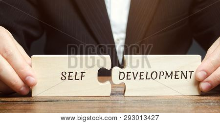 Businessman Collects Puzzles With The Word Self-development. Concept Of New Business Skills And Moti