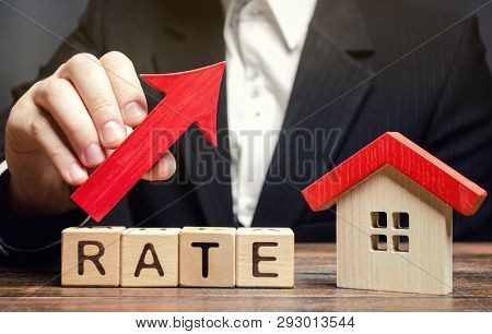 A Man Holds A Red Arrow Up Above The Word Rate And A Wooden House. The Concept Of Raising Interest R