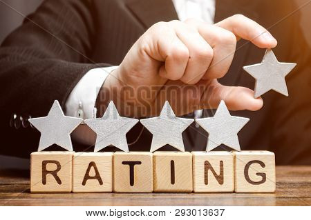Businessman Puts The Fifth Star Above The Word Rating On Wooden Blocks. The Concept Of The High Rati