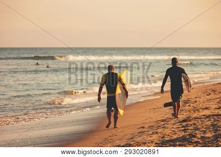 Two Adult Males With Their Surfboards Walk On The Beach In The Sand Towards A Great Surf Spot In Mal