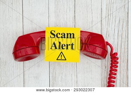 Scam Alert Message On Sticky Note On Retro Red Phone Handset On Weathered Whitewash Textured Wood Ba