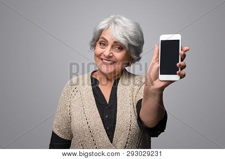 Pretty Senior Female In Elegant Clothes Cheerfully Smiling And Demonstrating Modern Smartphone With