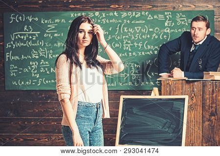 Young Female Student In Pink Cardigan And Blue Jeans Standing In Front Of Green Board. Brunette Teen