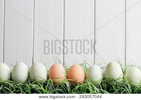 Natural Colored Easter Eggs In Grass Against A White Wooden Background With Room For Copy Space.