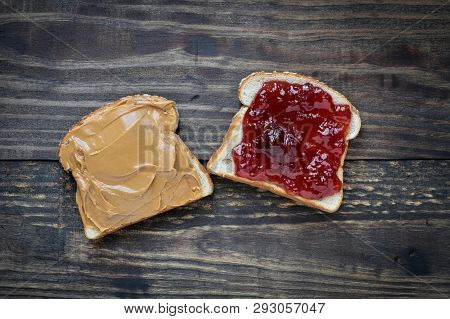 Top View Of Open Face Homemade Peanut Butter And Strawberry Jelly Sandwich On Oat Bread, Over A Rust