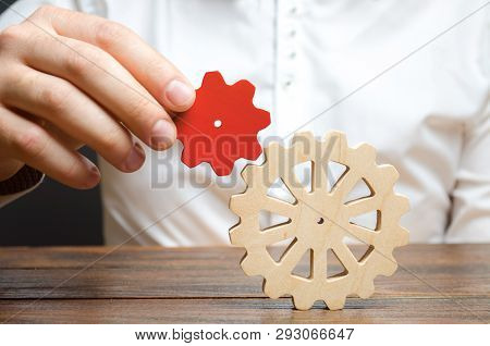 Businessman Connects A Small Red Gear To A Large Gear Wheel. Symbolism Of Establishing Business Proc