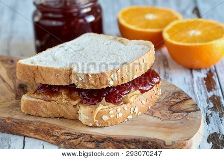 Homemade Peanut Butter And Jelly Sandwich On Oat Bread, Over A Rustic Wooden Background With Fruit I