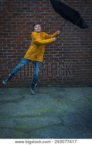 Boy With Raincoat And Umbrella Being Blown Away By A Storm
