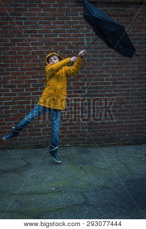 boy with raincoat and umbrella being blown away by a storm poster