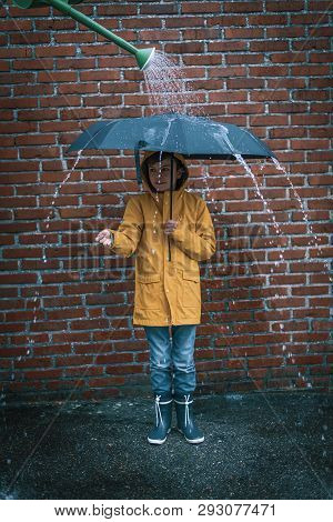 Boy With Raincoat Standing Under An Umbrella With A Watering Can Above Him For Some Fake Rain