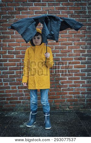 Boy Looking Sad Under A Teared Up Umbrella In Front Of A Bricl Wall