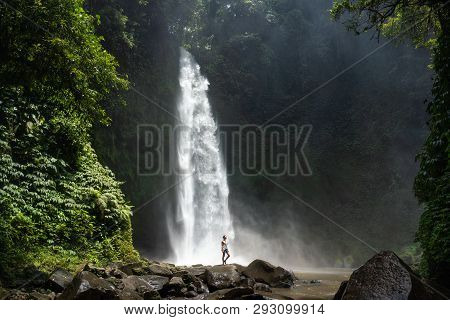 Adventure Seeker At Beautiful Jungle Waterfall And Enjoying Nature.
