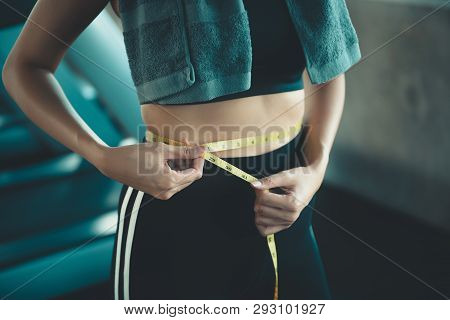 Portrait Of Beautiful Woman Showing Successful Weight Loss With Measuring Tap In Fitness Gym Backgro