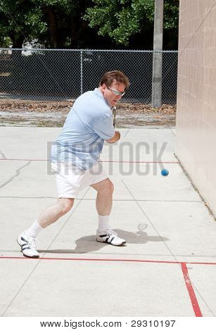 Mid adult man playing a fierce game of racquetball.
