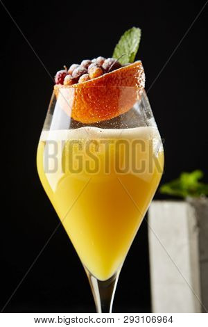 Paradise Cocktail with Gin, Yellow Peach, Mint and Red Berries in Elegant Tall Glass in Restaurant Close Up on Dark Background. Macro Photo of Exquisite Serving Fruit Alcohol Drink poster